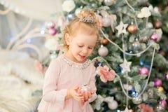 在圣诞节冷杉木附近的小女孩 免版税库存照片