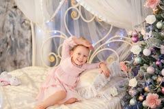在圣诞节冷杉木附近的小女孩 免版税库存图片