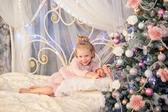在圣诞节冷杉木附近的小女孩 库存照片