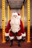 在圣诞节前的圣诞老人训练在健身房- kettlebells 免版税库存照片