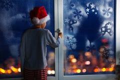 在圣诞节前的男孩在与雪花的窗口附近 库存照片
