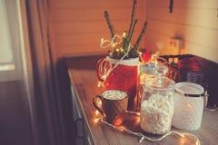 在圣诞节和新年假日装饰的乡间别墅厨房 Marhmallows、蜡烛、可可粉和坚果在现代瓶子 图库摄影