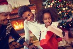 在圣诞节大气的愉快的微笑的非裔美国人的家庭 免版税库存照片