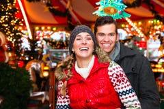 在圣诞节市场或出现季节期间的夫妇 库存图片