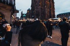 在圣诞节市场期间的旅游赞赏的Notre Dame大教堂 免版税库存照片