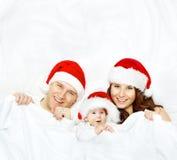 在圣诞节帽子、婴孩孩子、母亲和父亲的家庭白色的 免版税库存照片