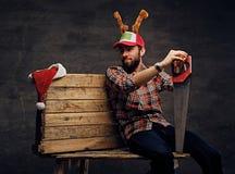 在圣诞节帽子的一个有胡子的男性有鹿` s垫铁的拿着手锯 免版税库存图片