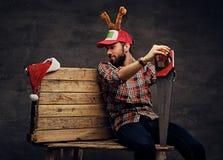 在圣诞节帽子的一个有胡子的男性有鹿` s垫铁的拿着手锯 免版税图库摄影