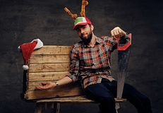 在圣诞节帽子的一个有胡子的男性有鹿` s垫铁的拿着手锯 库存图片