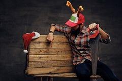 在圣诞节帽子的一个有胡子的男性有鹿` s垫铁的拿着手锯 免版税库存照片