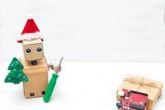 在圣诞节帽子的一个机器人握一把螺丝刀和a.c.的枝杈 免版税库存图片