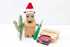 在圣诞节帽子的一个机器人握一把螺丝刀和a.c.的枝杈 免版税库存照片