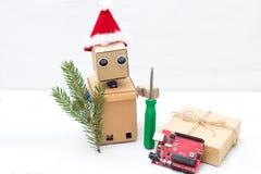 在圣诞节帽子的一个机器人握一把螺丝刀和a.c.的枝杈 库存图片