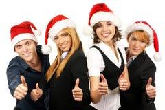 在圣诞节帽子的四愉快的businesspersons 库存照片