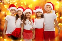 在圣诞节帽子的愉快的孩子有五颜六色的光的 免版税库存照片