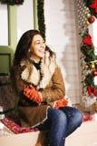 在圣诞节微笑在家装饰的愉快的女孩 免版税图库摄影