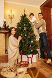 在圣诞节房子内部的家庭 库存图片