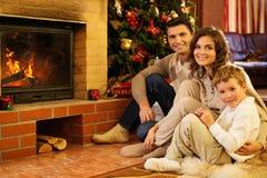 在圣诞节房子内部的家庭 免版税库存图片