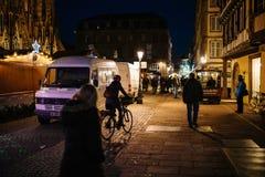 在圣诞节摊位附近走在nig的步行者和骑自行车者 免版税图库摄影
