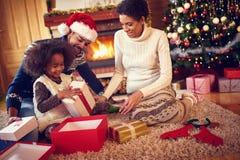 在圣诞节早晨打开的礼物的愉快的家庭 免版税库存照片