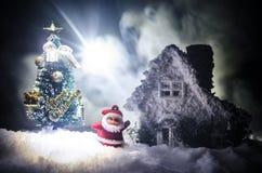 在圣诞节时间的愉快的圣诞老人玩偶与树和雪 五颜六色背景的bokeh 圣诞老人和圣诞快乐模型无花果 图库摄影