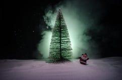 在圣诞节时间的愉快的圣诞老人玩偶与树和雪 五颜六色背景的bokeh 圣诞老人和圣诞快乐模型无花果 免版税图库摄影