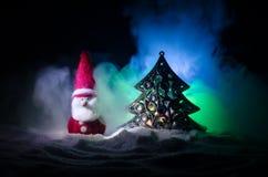 在圣诞节时间的愉快的圣诞老人玩偶与树和雪 五颜六色背景的bokeh 圣诞老人和圣诞快乐模型无花果 库存照片