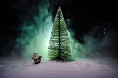 在圣诞节时间的愉快的圣诞老人玩偶与树和雪 五颜六色背景的bokeh 圣诞老人和圣诞快乐模型无花果 免版税库存照片