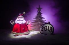 在圣诞节时间的愉快的圣诞老人玩偶与树和雪 五颜六色背景的bokeh 圣诞老人和圣诞快乐模型无花果 库存图片