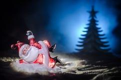 在圣诞节时间的愉快的圣诞老人玩偶与树和雪 五颜六色背景的bokeh 圣诞老人和圣诞快乐模型无花果 免版税库存图片