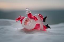 在圣诞节时间的愉快的圣诞老人玩偶与树和雪 被弄脏的室外背景 圣诞老人和圣诞快乐模型fi 库存照片