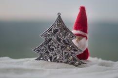在圣诞节时间的愉快的圣诞老人玩偶与树和雪 被弄脏的室外背景 圣诞老人和圣诞快乐模型fi 免版税图库摄影