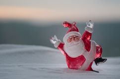 在圣诞节时间的愉快的圣诞老人玩偶与树和雪 被弄脏的室外背景 圣诞老人和圣诞快乐模型fi 免版税库存照片
