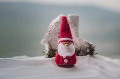 在圣诞节时间的愉快的圣诞老人玩偶与树和雪 被弄脏的室外背景 圣诞老人和圣诞快乐模型fi 图库摄影