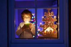 在圣诞节时间的小男孩支持的窗口 图库摄影