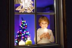 在圣诞节时间的小男孩支持的窗口 免版税库存图片