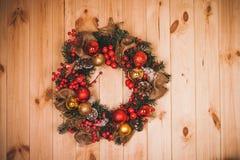 在圣诞节期间的大人为盘旋的花圈在门 免版税库存照片