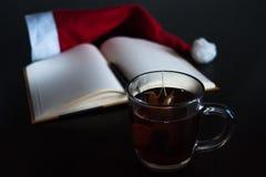 在圣诞节概念的计划未来:有空白页的一个笔记本,一支黑笔,圣诞老人帽子,有茶袋的,全部玻璃杯子在黑暗的dini 图库摄影