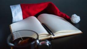 在圣诞节概念的计划未来:有空白页的一个笔记本,一支黑笔,圣诞老人帽子,有茶袋的,全部玻璃杯子在黑暗的dini 库存图片