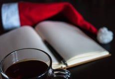 在圣诞节概念的计划未来:有空白页的一个笔记本,一支黑笔,圣诞老人帽子,有茶袋的,全部玻璃杯子在黑暗的dini 免版税库存图片