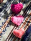 在圣诞节毛线衣的桃红色心脏 免版税图库摄影