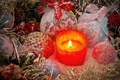 在圣诞节玩具和球围拢的雪的圣诞节蜡烛 库存照片