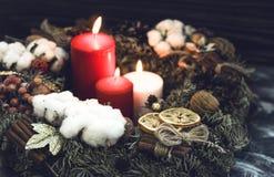 在圣诞节的两个红色和一白色蜡烛缠绕 免版税库存图片