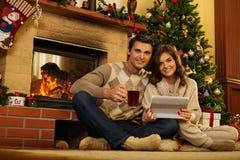 在圣诞节的夫妇装饰了房子 库存图片