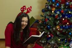 在圣诞节的女孩读书 库存图片