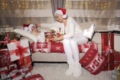 在圣诞节的妈妈和女儿充分的幸福,享用礼物 库存照片