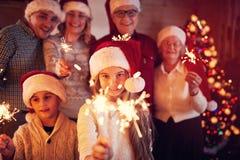 在圣诞节的家庭与滑稽的闪烁发光物 库存照片