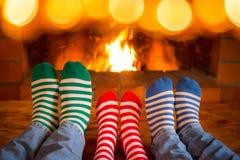 在圣诞节的家庭在壁炉附近殴打 免版税库存图片