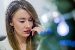 在圣诞节的富有思想的妇女阅读书装饰了得在家 假日概念、圣诞节、假日和人概念 图库摄影
