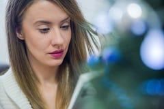 在圣诞节的富有思想的妇女阅读书装饰了得在家 假日概念、圣诞节、假日和人概念 免版税库存照片